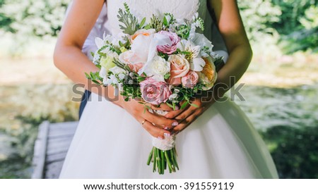 A nice wedding bouquet of purple, pink and white peonies hold by a bride