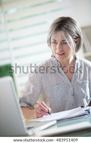 a nice woman of 40 years with gray hairs who works at home with a laptop and a tablet. she is a self employed and she like what she does it,she's absorbed by her work. she is at foreground
