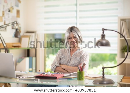 a nice 40 year old woman, she is sitting at her desk, she is doing her accounts and she needs glasses  because she is presbyopic. she is relaxed, she is laughing