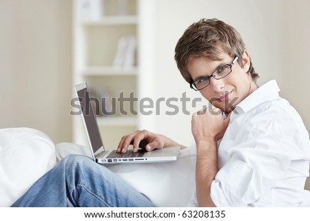 A nice young man with a laptop at home