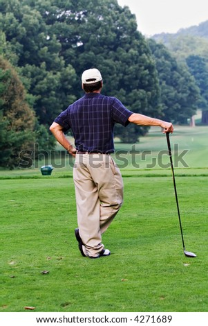 A nicely dressed male golfer waiting for the fairway to clear so that he can make his long drive from the tee. - stock photo