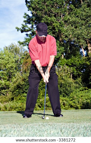 "A nicely dressed male ""pro"" golfer about to hit the ball. - stock photo"