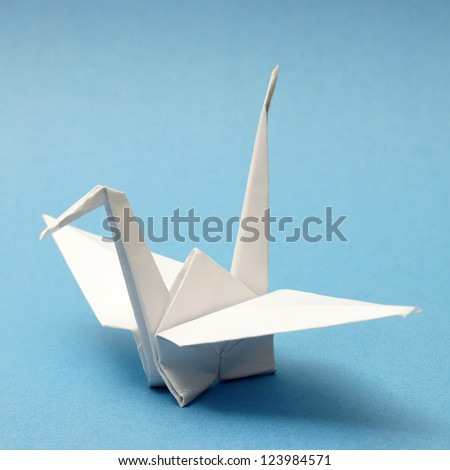 A nicely folded origami swan over a blue tranquil background. - stock photo