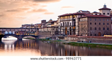 A night scene at sunset of the Ponte Vecchio bridge over the Arno River in Florence, Italy. The bridge is made of stone and houses many tourist shops, jewelers and art dealers. - stock photo