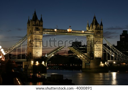 a night shot of tower bridge with the bridge raised
