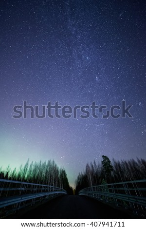 A night sky full of stars and visible milky way with a bridge on foreground. Green light of the northern lights on th left side of the sky. - stock photo
