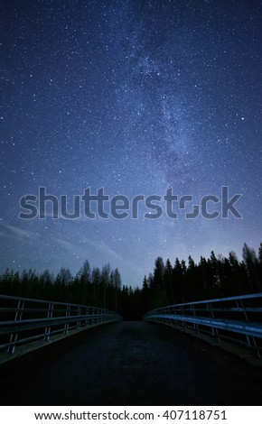 A night sky full of stars and visible milky way with a bridge on foreground. Road leading to dark forest. - stock photo