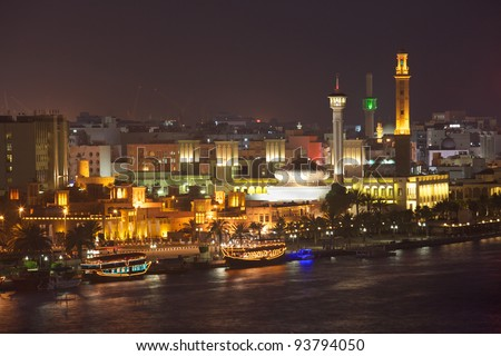 A night-time view of dhow restaurants on Dubai Creek, with the historic district of Bastakiya in the background. - stock photo