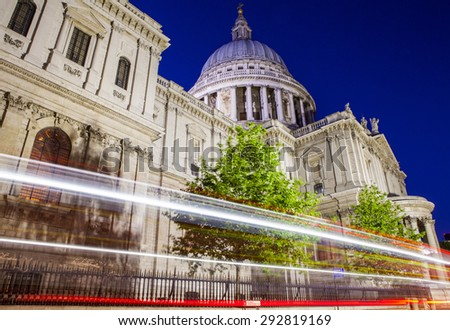 A night-time view of light trails passing the historic St. Pauls Cathedral in London. - stock photo