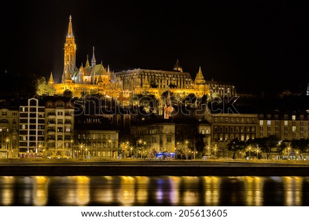 A night view from the danube river of the Mathias Church in Budapest (Hungary) or Church of Our Lady: red and orange diamond patterned roof tiles, neo-Gothic rose window and towers under dark night  - stock photo