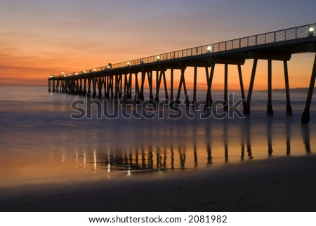 a night view of a beach with a pier extending into the ocean - stock photo