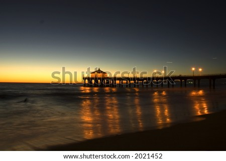 a night view of a pier and the ocean with reflected lights. - stock photo