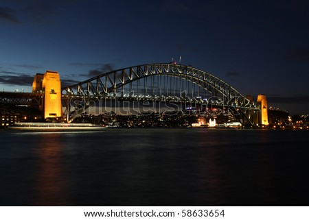 """A night view of one of Sydney's most famous landmarks. The Sydney Harbour Bridge. The bridge was opened in 1932 and is well known by its nick name of """"the coathanger"""" Ferry light blur mid-frame. - stock photo"""