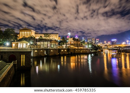 A nighttime view of the Philadelphia Museum of Art, with the city skyline behind it. - stock photo