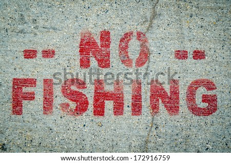 A No Fishing Sign Stamped Onto Cement By Ocean Or River - stock photo