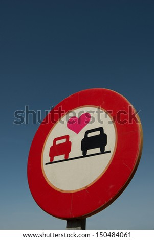 A no overtaking road sign with a love heart - stock photo