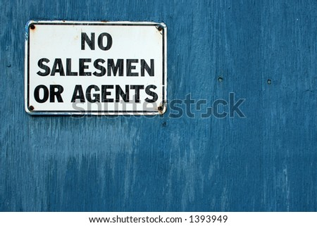 "A ""No Salesmen"" sign on a weathered blue door. - stock photo"