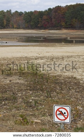 A no swimming sign in front of a dried up drought stricken lake.  Focus on the sign. - stock photo