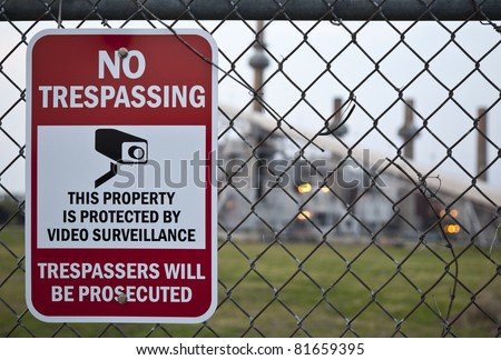 A no trespassing Sign on a fence with a power plant in the background. - stock photo