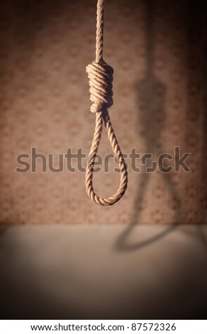 A noose hanging in a dark room. - stock photo