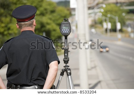A North American policeman waits to catch speeding drivers with a radar gun. (Shot with minimum depth of field. Focus is on the police officer and radar gun.) - stock photo