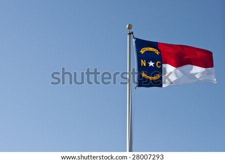 A North Carolina State Flag waving in the wind against a clear blue sky.