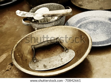 A nostalgic image of authentic old fashioned, vintage cooking or baking utensils and dishes in the middle of being used to create a homemade recipe (shallow depth of field, sepia/brown tint). - stock photo