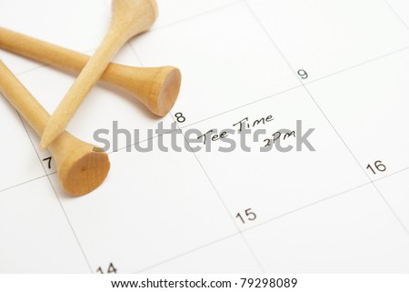 A note on a calendar reminds a golfer of his afternoon game to be played. - stock photo