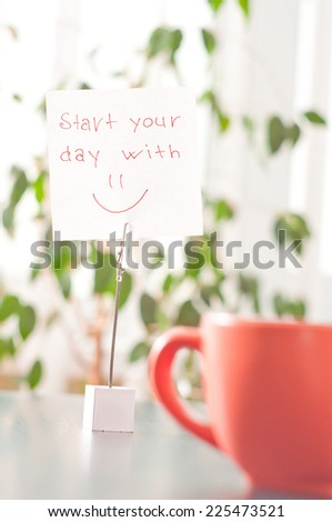 a note on the table start your day with a smile - stock photo