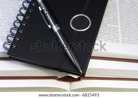 a notebook and a pen lying on the pile of books - close up - stock photo