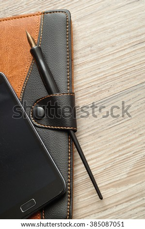 A notebook displayed with a smart phone and a fountain pen on a wooden table - stock photo