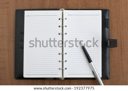 A notebook in a file with a silver pen. - stock photo
