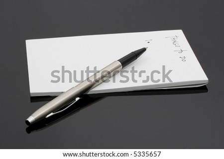 A notepad and a pen on a black background