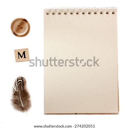 A notepad of recycled paper with retro objects: a button, a stamp for the letter m and a feather - stock photo