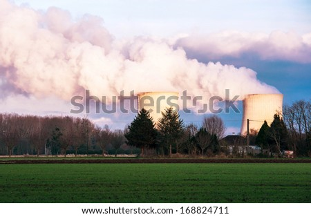 A nuclear power plant located in the countryside close to homes - stock photo