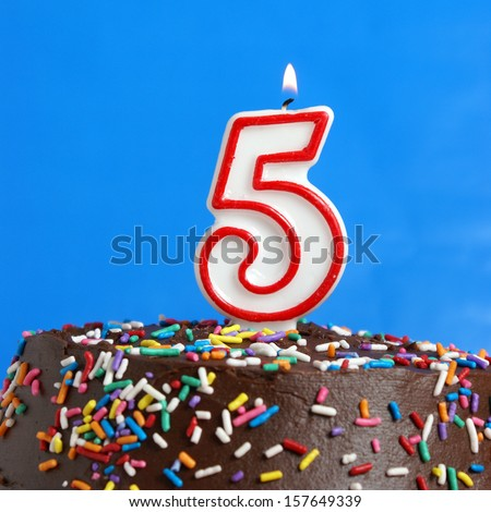 A number candle is lit in celebration of five years. - stock photo