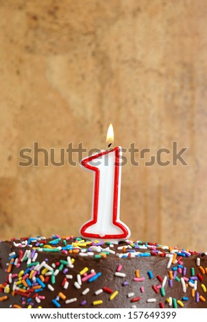 A number candle is lit in celebration of the first year. - stock photo