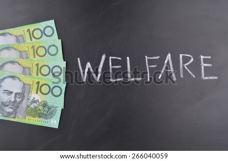 A number of one hundred Australian dollar notes on a blackboard where welfare is handwritten in white chalk - stock photo