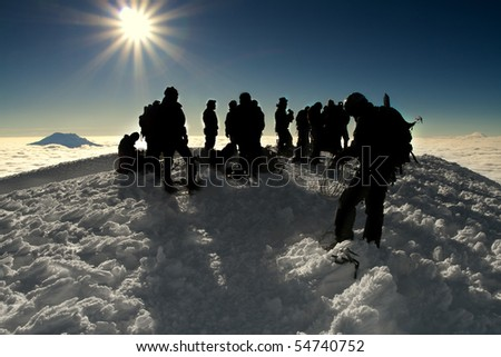 a number of silhouettes standing on the peak of cotopaxi, an ice packed mountain - stock photo