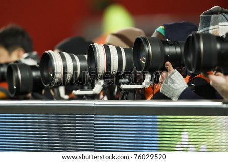 A number of super telephoto lenses in use for a sporting event. - stock photo