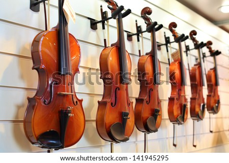 A number of violins hanging on the wall in the shop - stock photo