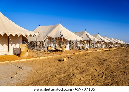 A number of white tents in Indian Thar desert, Desert national Park, blue sky and yellow sand in daylight, copy space