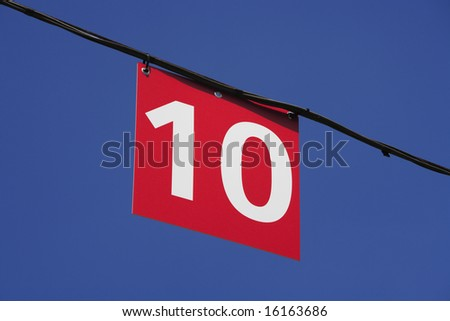 A number 10 sign suspended from a cable against a blue sky.