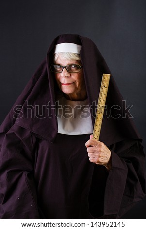 A nun brandishing a ruler - stock photo