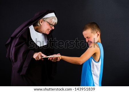 A nun hitting a boy on the knuckles with a ruler - stock photo
