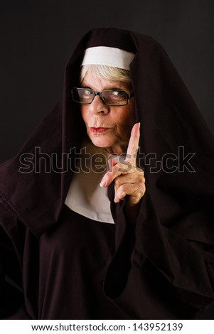 A nun holding up her finger in a gesture of patience. - stock photo