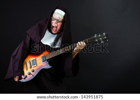 A nun jamming hard on an electric guitar - stock photo