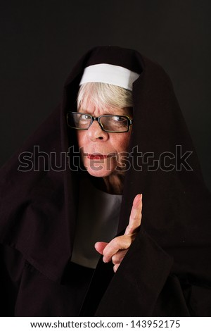 A nun with a disapproving expression wagging her finger. - stock photo