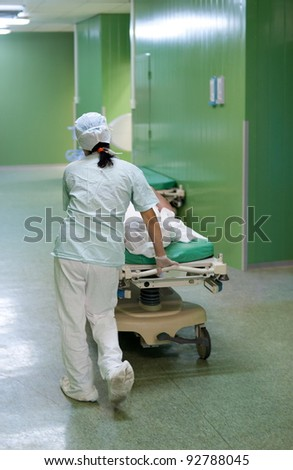 a nurse carries a patient on a gurney - stock photo