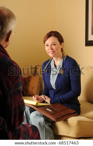 a nurse in scrubs in a home with a patient - stock photo